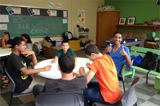 A group of teenagers seated at a table do an exercise for the Teen Empowerment Program