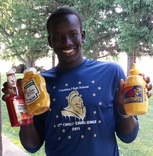 Garang, a teenage boy, smiles while holding bottles of ketchup and mustard