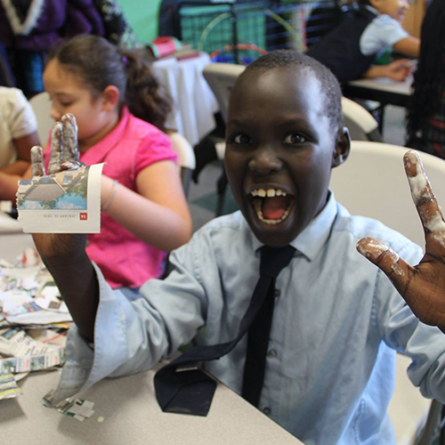 A young student makes a silly pose while making a paper mache craft