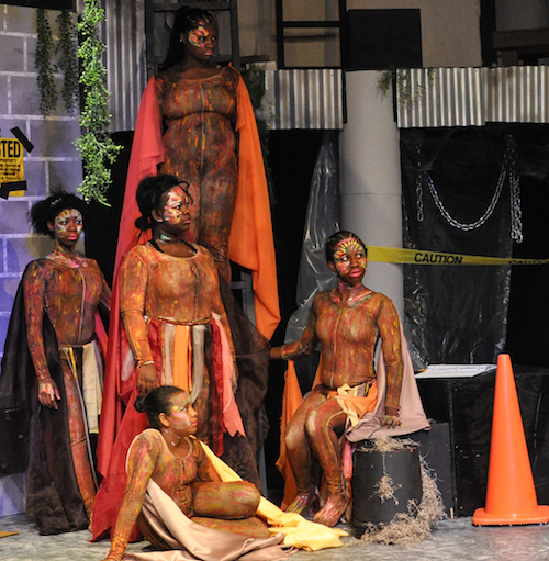 Students in colorful theater costumes perform on stage as part of the Theater For All program