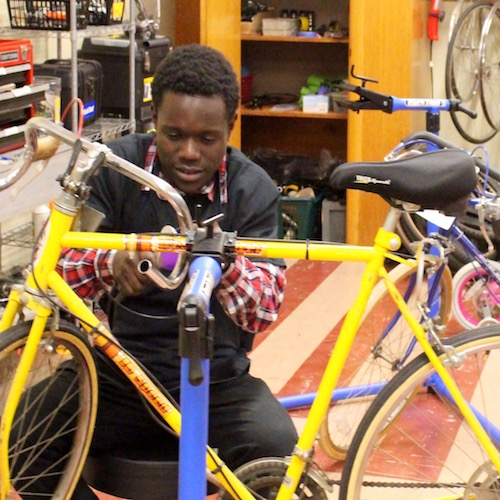 A young man works on repairing a bicycle as part of the City Bikes program