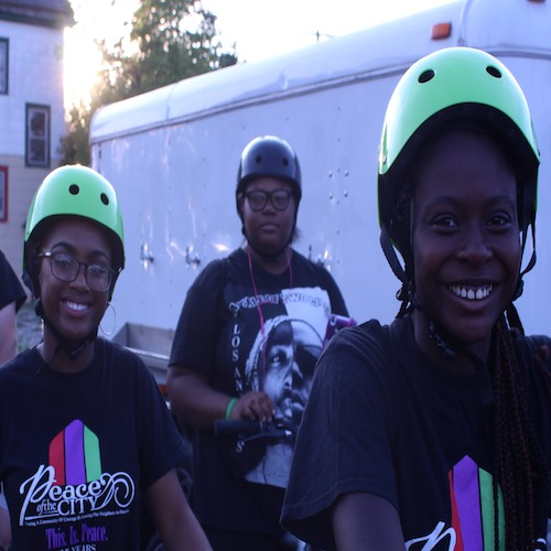 Three teenage girls in green helmets participate in a Peace of the City cycling event