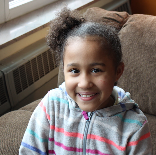 Young Saniah smiles brightly for a portrait, sitting on a brown couch