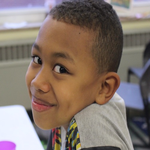 Savion smiles over his shoulder for a portrait in a school classroom