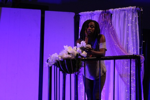 A student actress pauses on a balcony, the stage set lit with vibrant purple light