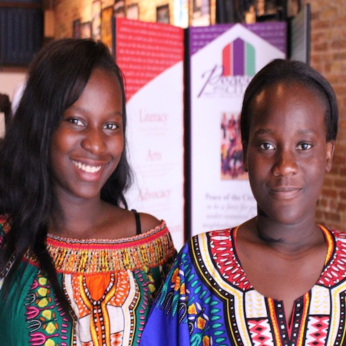 Two African girls in traditional dress smile at a Peace of the City event
