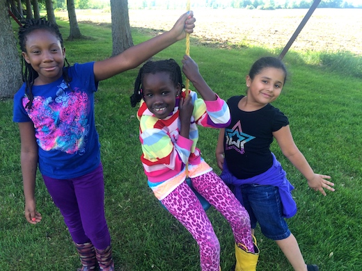 Three young girls play on a tire swing in a grassy yard