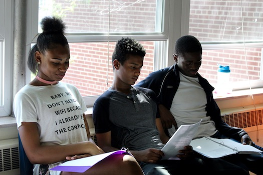 Three students study the script for their next theater performance