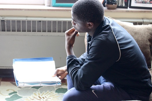 A young man studies a script intently, preparing for a theater performance