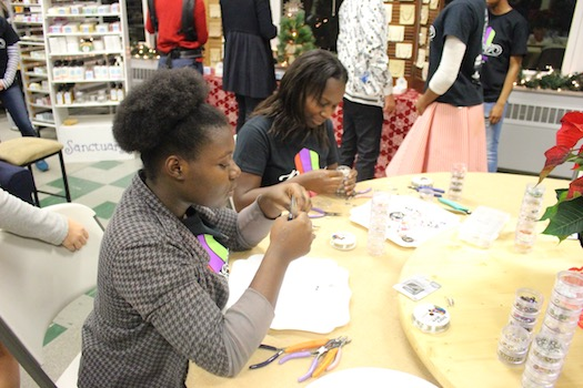 Women work together at a table to create hand-crafted jewelry pieces with Zieani Jewelry