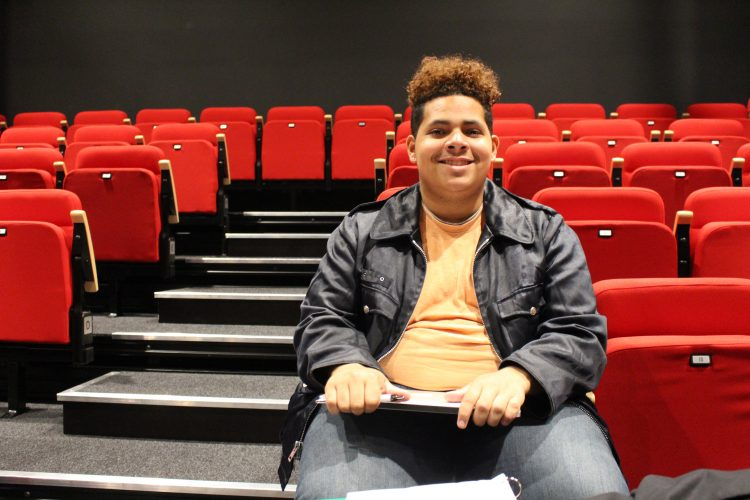 Jadon, a student actor, smiles and holds his script while seated among red folding theater seats