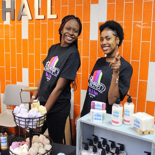 Two young women work at the Sanctuary Soaps and Fragrances display