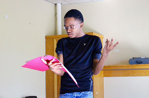 Larryn rehearses for a theater performance while holding a script
