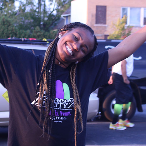 Larencia smiles and raises her arms at a Peace of the City cycling event