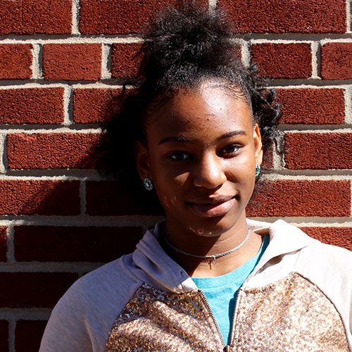 Larencia smiles for a spotlight portrait in front of a brick wall