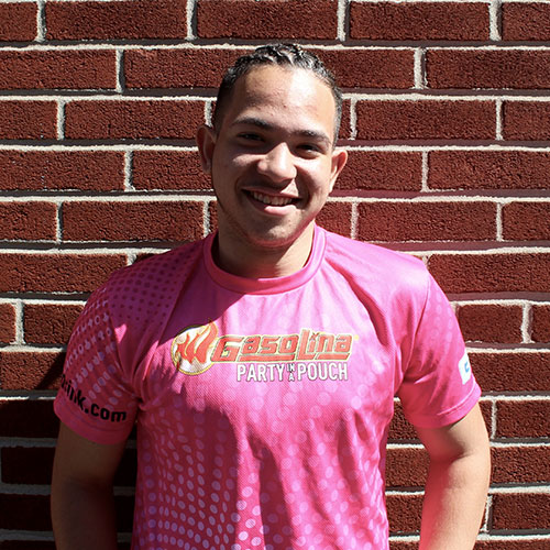 A young man in a pink shirt smiles for a spotlight portrait in front of a brick wall