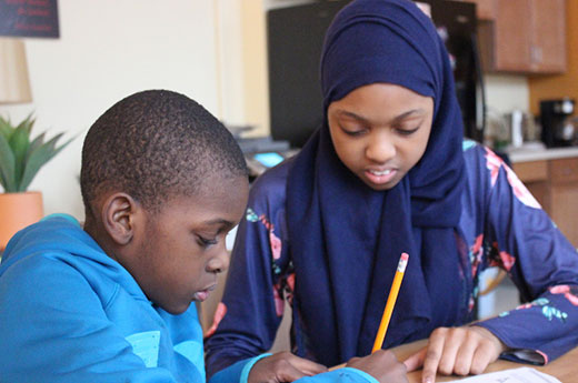 Khadija and a friend work on their homework during the Peace Club after-school program
