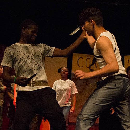 Two student actors perform a stage knife fight as part of their theater rehearsal