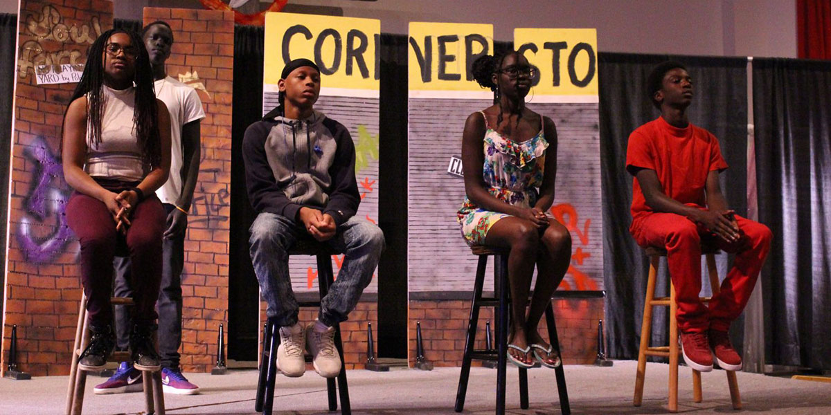 Four students sit on stools, about to perform monologues as part of the Ordinary Resurrections speaker series