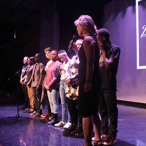 Students line up on stage, about to perform their Ordinary Resurrections monologues