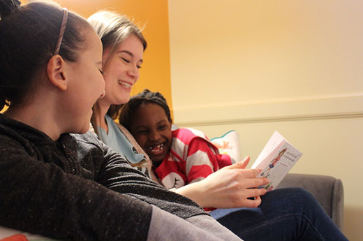 Sage reads a book to two young girls, sitting on a couch together and smiling